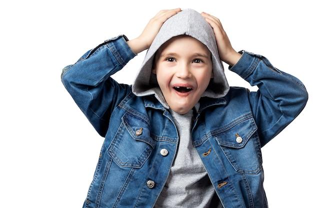 Menino sorridente com uma jaqueta jeans, segurando a cabeça, gritando alegremente sobre um fundo branco e isolado