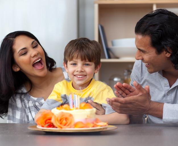 Menino sorridente comemorando seu aniversário com seus pais