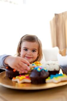 Menino sorridente comendo confeitaria em casa