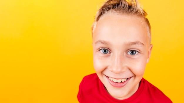 Menino sorridente de alto ângulo com fundo amarelo