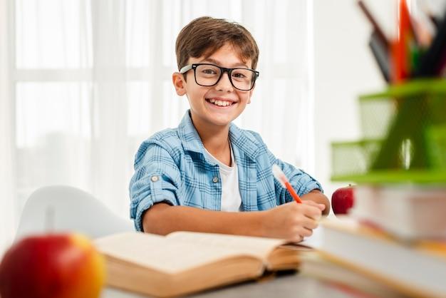 Menino sorridente de alto ângulo com óculos estudando