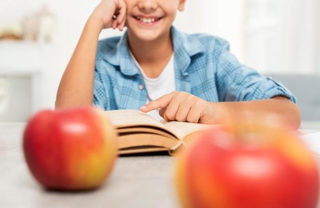 Menino sorridente de close-up em casa lendo
