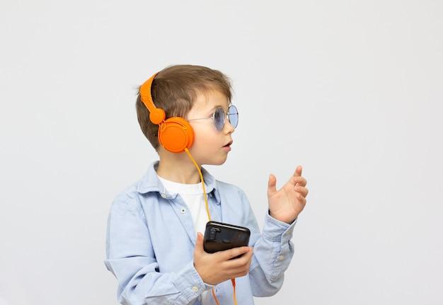 Menino sorridente de óculos escuros ouvindo música em fones de ouvido com o telefone