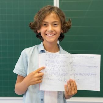 Menino sorridente de retrato mostrando a página com trabalhos de casa