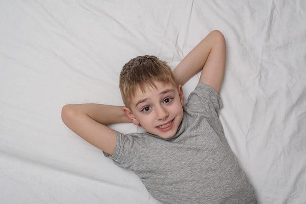 Menino sorridente, deitada na cama. vista superior, copie o espaço.