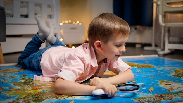 Menino sorridente deitado no chão no quarto de hos e explorando o grande mapa-múndi através da lupa. conceito de viagens, turismo e educação infantil. exploração e descobertas infantis.