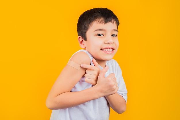 Menino sorridente depois de ter recebido a vacinação.