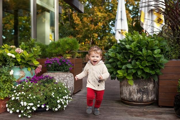 Menino sorridente é executado em uma terassa de café. criança adorável sorri e tem alegria. atividades ao ar livre para crianças