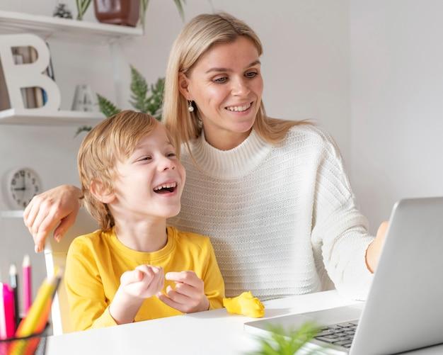 Menino sorridente e mãe usando laptop em casa