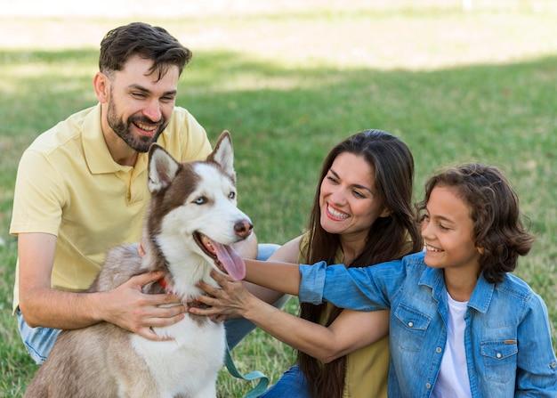 Menino sorridente e pais fazendo carinho no cachorro enquanto estão no parque
