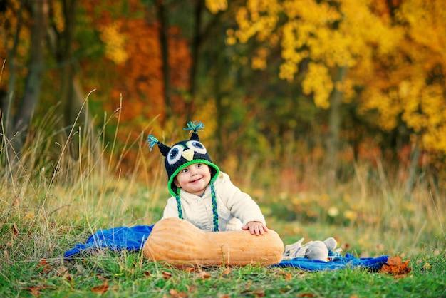 Menino sorridente em um boné de malha e roupas elegantes quentes, sentado na grama com árvores de abóbora e outono