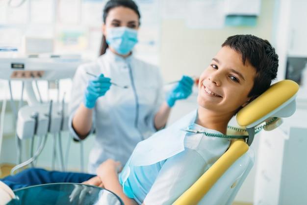 Menino sorridente em uma cadeira odontológica, odontopediatria profissional