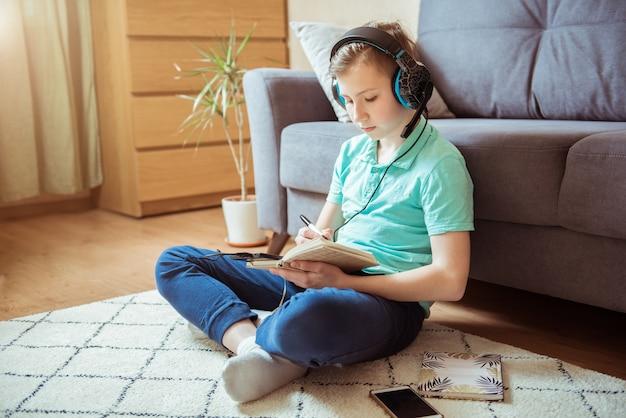 Menino sorridente faz sua lição de casa com fones de ouvido e um tablet