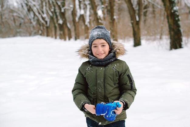 Menino sorridente feliz em roupas de inverno durante a caminhada
