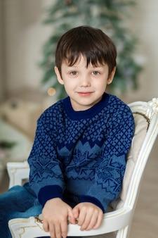 Menino sorridente feliz sentado na poltrona perto de árvore de natal e segurando a caixa de presente de natal.