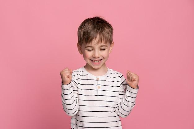 Menino sorridente isolado em rosa