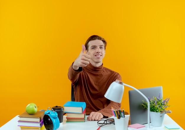 Menino sorridente, jovem estudante sentado à mesa com as ferramentas da escola, o polegar isolado na parede amarela