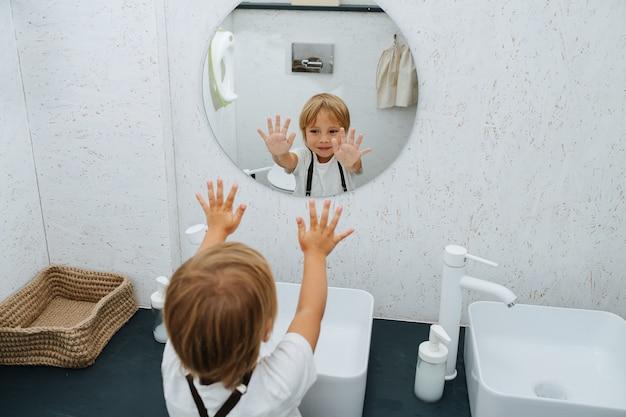 Menino sorridente, lavando as mãos na pia, acenando com as palmas limpas para um espelho