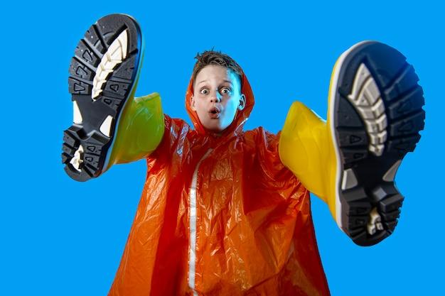 Menino sorridente na capa de chuva laranja enfiou as mãos em botas de borracha no fundo azul