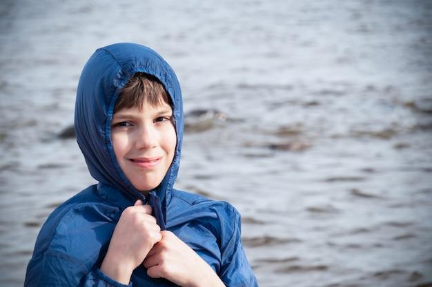 Menino sorridente na jaqueta azul com capuz no contexto do mar, o tempo frio.