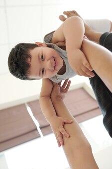 Menino sorridente nas mãos de um pai carinhoso e amoroso brincando com ele em casa