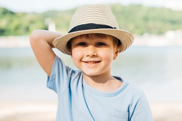 Menino sorridente no chapéu, aproveitando a luz do sol