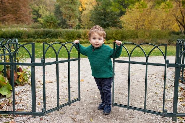 Menino sorridente no parque outono. criança adorável sorri e tem alegria. garotinho abrindo o portão do parque. atividades ao ar livre para crianças