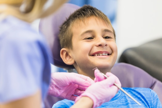 Menino sorridente, passando por tratamento odontológico na clínica