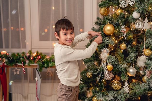 Menino sorridente pendurando uma bola decorativa na árvore de natal antes da festa de ano novo em casa