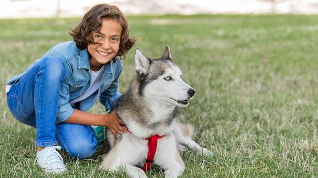Menino sorridente posando com um cachorro enquanto está no parque