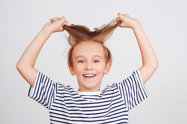 Menino sorridente, posando no estúdio. estilo e moda infantil. menino feliz com um penteado elegante. infância feliz e emoções positivas. expressão facial. retrato de menino engraçado. criança se divertindo e rindo.