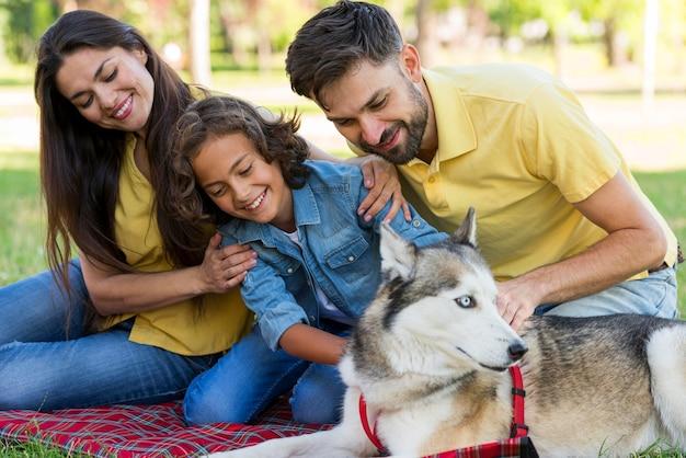 Menino sorridente posando no parque com o cachorro e os pais