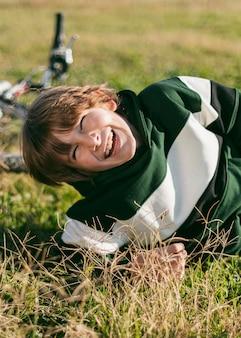 Menino sorridente relaxando na grama enquanto anda de bicicleta