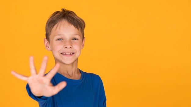 Menino sorridente segurando a mão para a frente com espaço de cópia