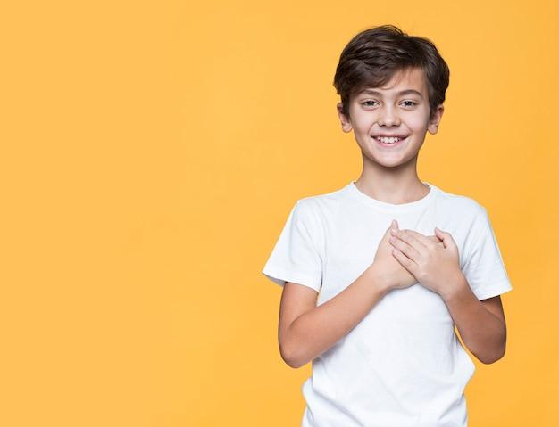 Menino sorridente, segurando as mãos no lugar do coração