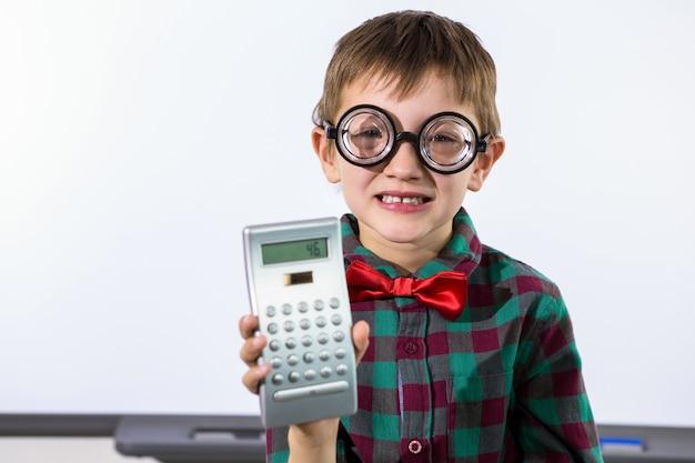 Menino sorridente, segurando calculadora, em, sala aula