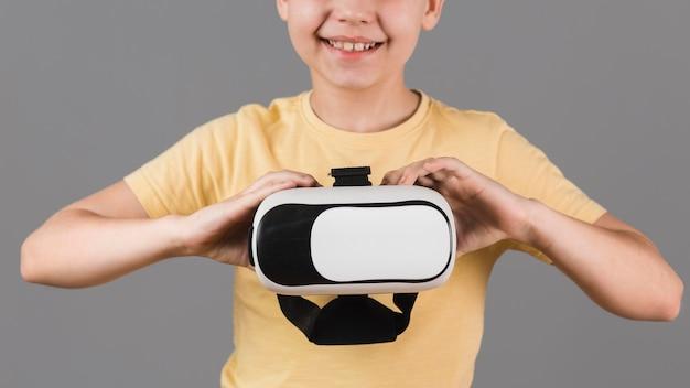 Menino sorridente segurando fone de ouvido de realidade virtual