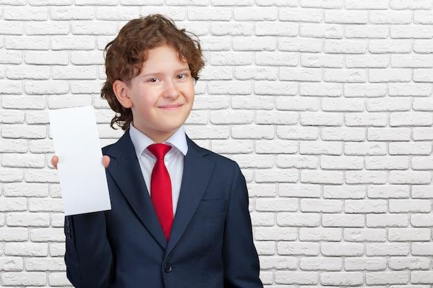 Menino sorridente, segurando o papel em branco