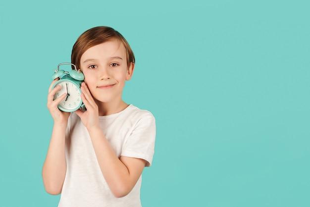 Menino sorridente segurando o relógio despertador. conceito de gerenciamento de tempo. aluno com relógio retrô sobre fundo de cor. conceito de tempo. zombe, copie o espaço. hora da escola.