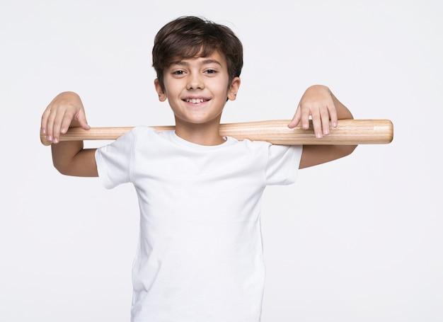 Menino sorridente segurando o taco de beisebol