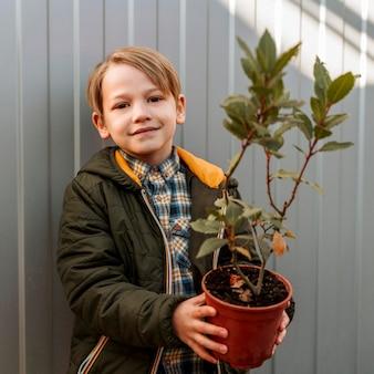 Menino sorridente segurando o vaso com uma pequena árvore