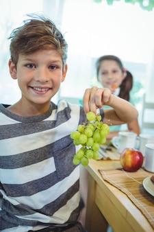 Menino sorridente segurando um cacho de uvas