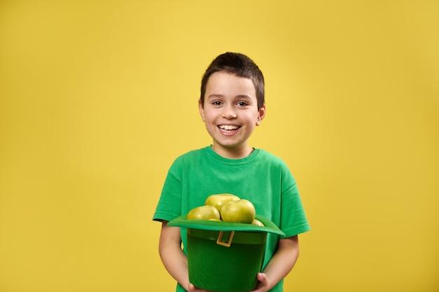 Menino sorridente segurando um chapéu irlandês de duende verde cheio de maçãs e sorrindo para a câmera