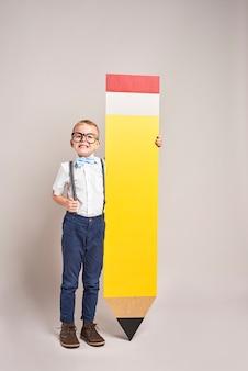 Menino sorridente segurando um grande lápis