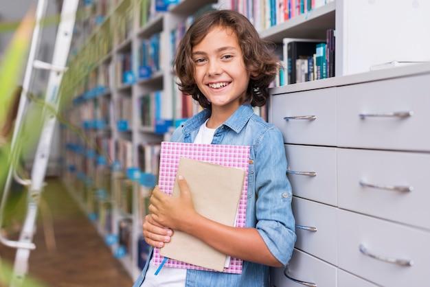 Menino sorridente segurando um livro e um caderno na biblioteca