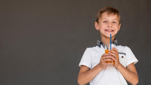 Menino sorridente segurando um suco de laranja com espaço de cópia