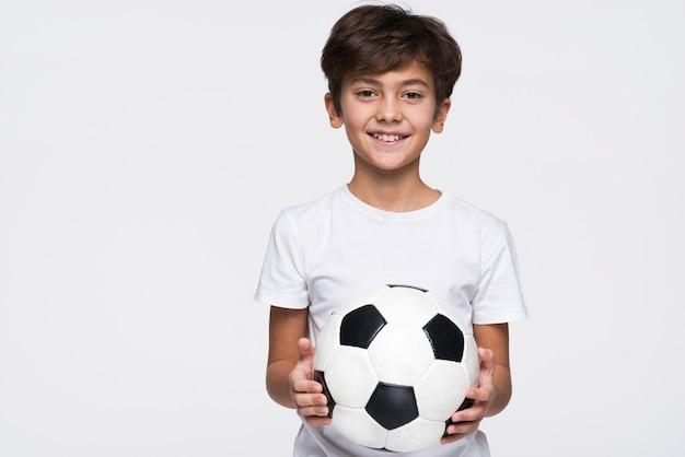Menino sorridente, segurando uma bola de futebol