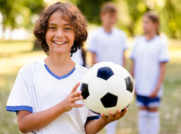 Menino sorridente segurando uma bola de futebol