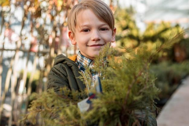 Menino sorridente segurando uma pequena árvore em um vaso