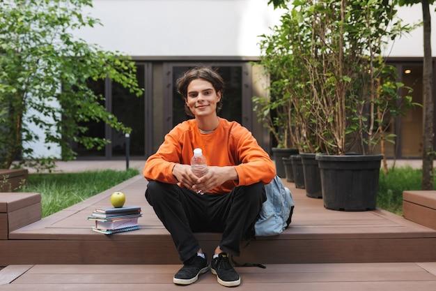 Menino sorridente sentado com uma garrafa de água nas mãos e livros perto e alegremente no pátio da universidade